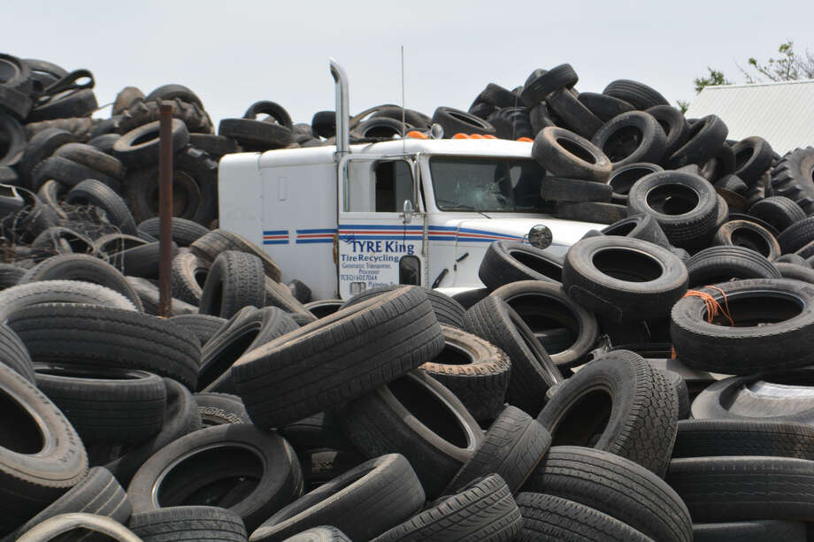 Doug McDonough/Plainview HeraldA Tyre King truck-tractor is largely buried by a sea of junk tires at 34th and Wood. A district court judge in Travis County has ordered owner Santos Barcenas to remove all except 500 within six months.
