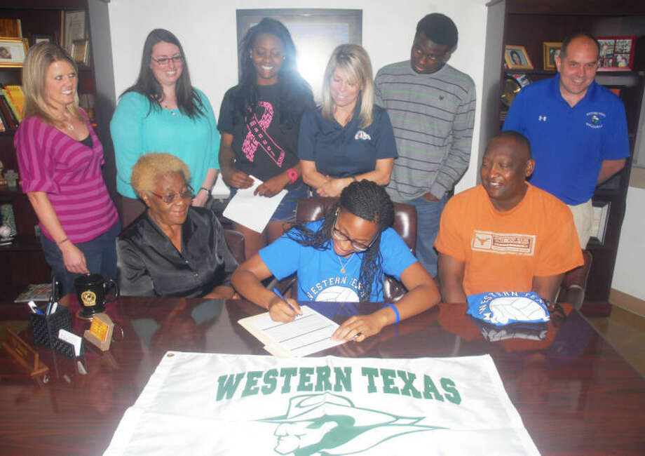 With family and coaches gathered around, Plainview High School senior Taivia Hearn signs a letter of intent Tuesday to play volleyball for Western Texas College in Snyder next year. Photo: Homer Marquez/Plainview Herald