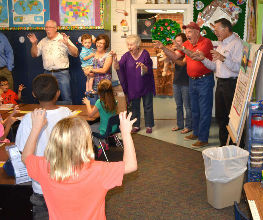 Local Lions Club members Eddie Carter (left), Linda Murphree, Andrea Ingram, Lions Queen Meredith McDonough, Larry McNutt and Paul Drager show first graders at Hillcrest School how to roar like a Lion on Wednesday after giving each their own book to read this summer. The club distributed free books to all first graders in Plainview public schools this week in an annual service project.