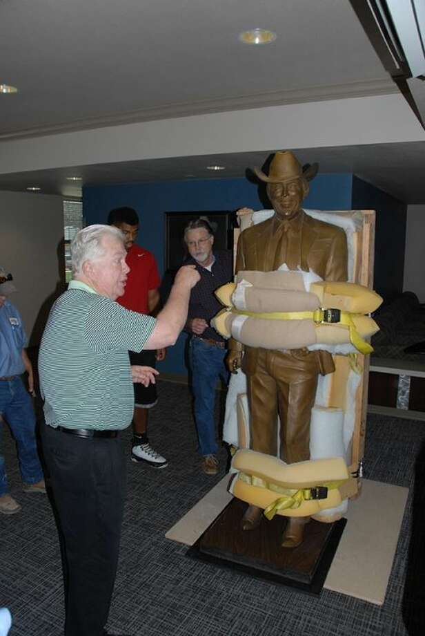 t University Executive Director of Advancement Mike Melcher instructs workers on where to place the 800-pound Jimmy Dean statue in its temporary home in Jimmy Dean Hall. The statue will be moved to the Jimmy Dean Museum when it is complete in August 2015.