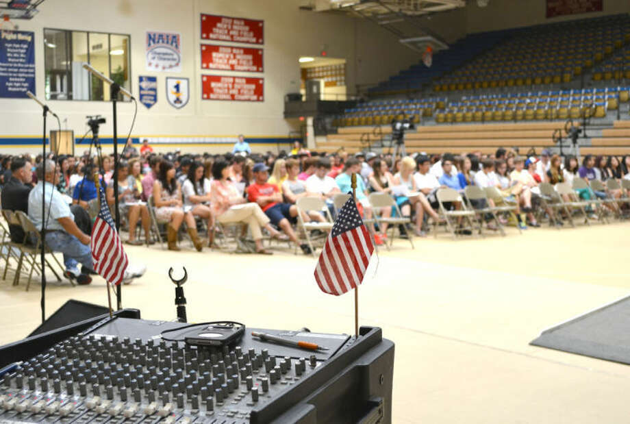 Doug McDonough/Plainview HeraldMiniature American flags decorate the sound board that awaits Plainview High choir director Walter Wright as graduating seniors listen in instructions during a rehearsal Thursday for tonight's ceremony, which begins at 7 p.m. at Hutcherson Center. (Photo gallery at www.MyPlainview.com.)