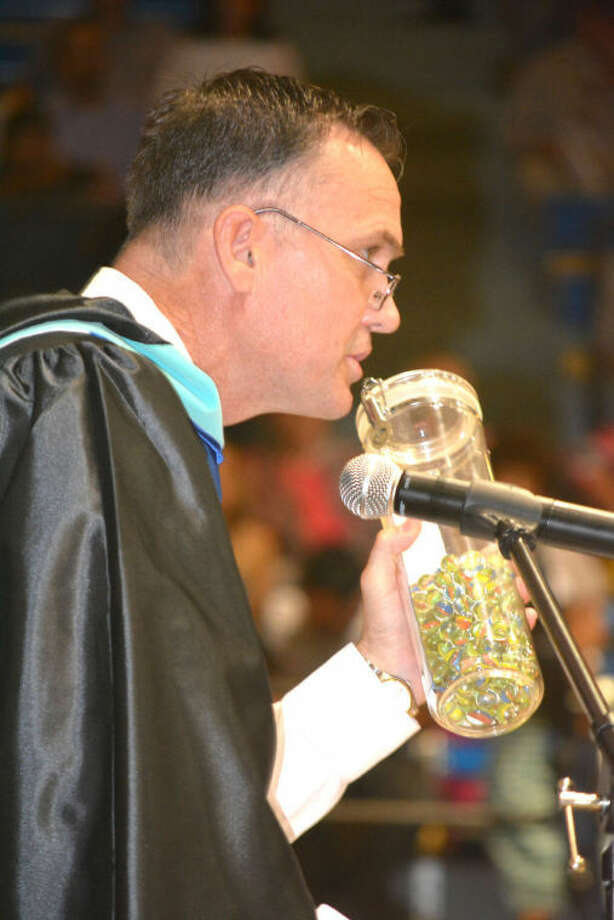 Rogers holds a jar of marbles collected from many of the 320 seniors as they were presented their diplomas.