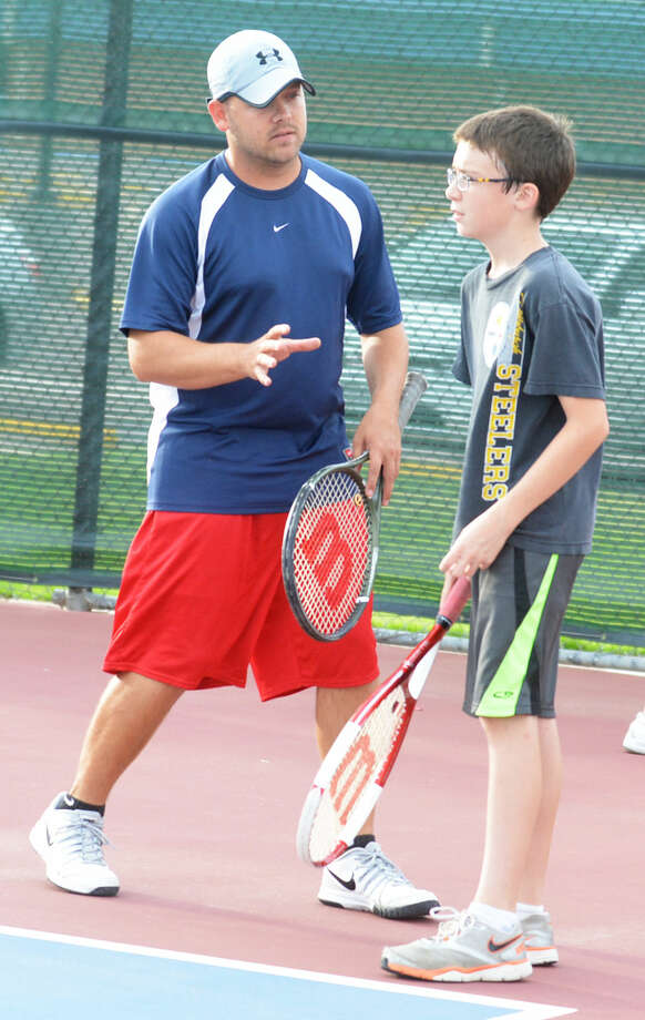 Plainview High School tennis coach Jonathan King (left) explains one of the finer points of the game to a youngster during the PISD tennis camp last year. Signups are currently ongoing for the camp for elementary school students, which will be June 1-5 from 6-8 p.m. at the PHS tennis courts. Photo: Skip Leon/Plainview Herald