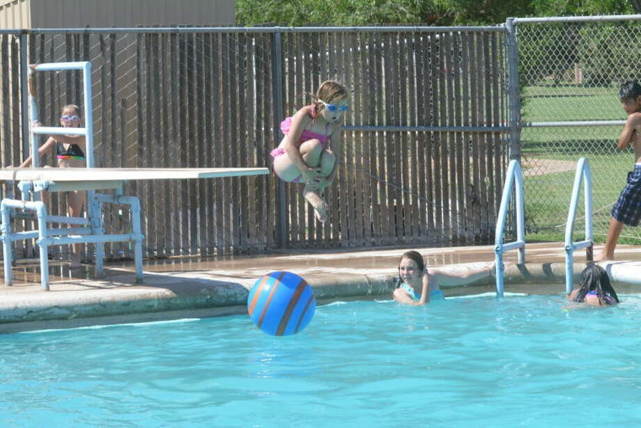 Kenadee Black waits her turn to jump as Kamryn Hembree does a cannonball into the 16th Street Pool in Plainview. Locals tried anything they could to beat the heat as the temperature Wednesday afternoon hit a record 107. Photo: Homer Marquez/Plainview Hearld