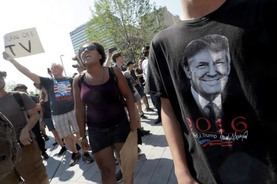 A Black Live Matter protestors shouts slogans standing next to next to a supporter of Republican presidential candidate Donald Trump in Public Square on Tuesday, July 19, 2016, in Cleveland, during the second day of the Republican convention. (AP Photo/Mary Altaffer) Photo: Mary Altaffer, Associated Press / AP