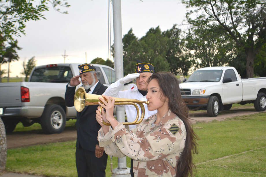 "American Legion representatives Alfred Mesra (left) and Ralph Langley salute as 16-year-old Nicolette Duquette plays ""Taps"" to conclude Monday's Memorial Day Ceremony at Plainview Cemetery. Her father, Sgt. Darrell Duquette, served in both Desert Storm and Desert Shield, before dying of cancer in 2000."