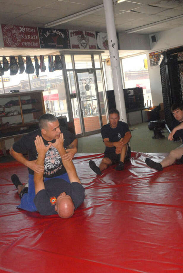 Plainview Detective Al Longoria, on top, teaches a shift of Plainview firefighters the basics of self-defense Wednesday afternoon. Photo: Homer Marquez/Plainview Herald