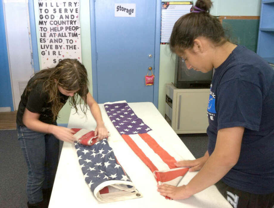 Anna Marie Rushin (left) and Beatrice Rodriquez, members of Girl Scout Troop 6151, fold American flags as prescribed by U.S. Flag Code where they will end up as familiar triangles. Their troop is among several local organizations participating in a flag retirement ceremony, set for June 15. Photo: Crystal Rushin/Girl Scout Troop 6151