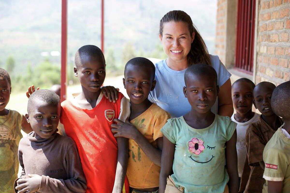Linnea Davis, a Stanwich librarian, poses with students from the Blessing School in Rwanda. Davis and other staff members, along with two groups of students, spent weeks in the country helping build and renovate the school.