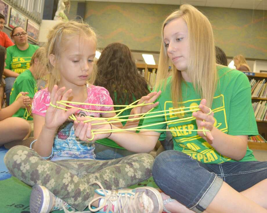 Pulling StringsDoug McDonough/Plainview HeraldJunior Literacy Council member Pennington Moore, a senior at Plainview Christian High School, helps 8-year-old Lianna Jones master the art of string figures during Wednesday's Texas Reading Club at Unger Memorial Library. The library's summer reading program runs from 10-11 a.m. Mondays, Wednesdays and Fridays through June for kids going into the third grade and up. A concurrent program, the Read-to-Me Club, is for children ages 4 to 7 years and meets in in the library basement. Friday's program will conclude a section on string figures. On Monday, participants will learn about kids' health from Coralyn Dillard of Covenant Health Plainview, with Laura Summers talking about allergies on Wednesday.