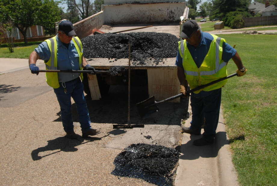 City employees Felix Rodriguez and Lee Galvan work to fill a pothole at Eighth and Kokomo streets. Photo: Homer Marquez/Plainview Herald