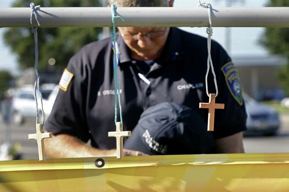 Millville, N.J., police chaplain Robert Ossler prays at a makeshift memorial at the shooting scene in Baton Rouge, La. On Sunday, three Baton Rouge police officers were murdered by a gunman. Our nation must get serious about confronting the cycle of violence. Photo: Gerald Herbert /Associated Press / AP
