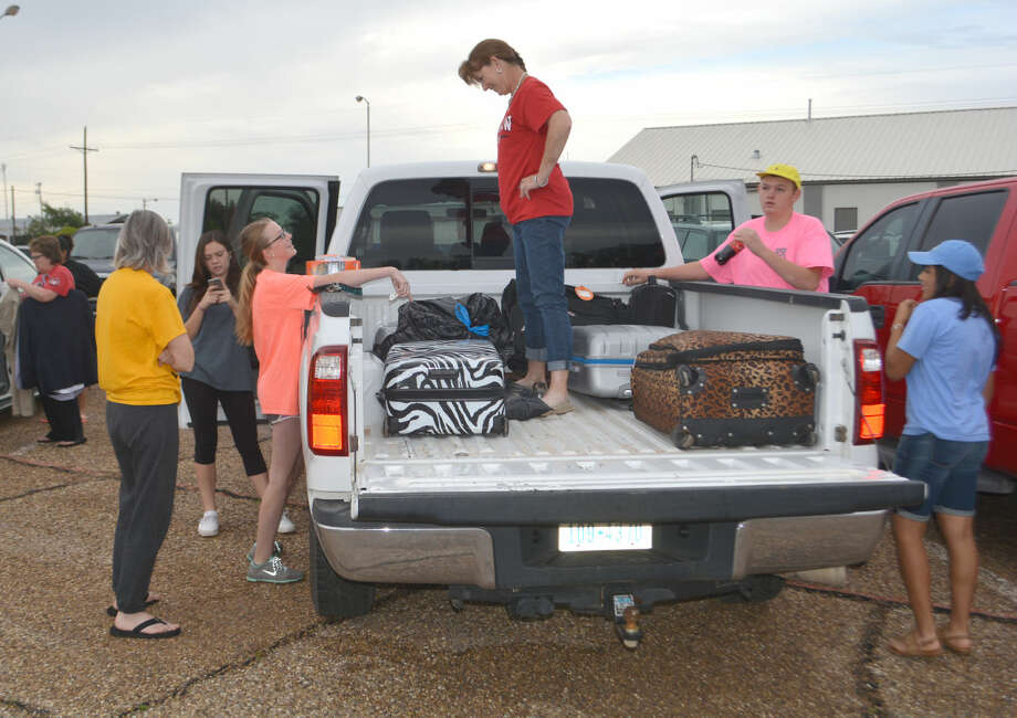 Doug McDonough/Plainview Herald Colti Wright (left) and Lisa Wright have a mother-daughter moment while loading luggage early Monday for a trip to State 4-H Roundup in College Station.