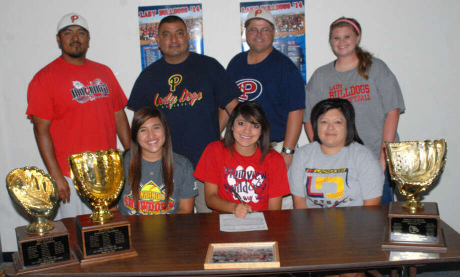 Plainview softball player Averee DeLuna (seated, center) signs a letter of intent to play at Western Texas College in Snyder next season. Also seated are her Lady Bulldog teammate Lori Gonzalez (left) and her mom, Tammy. Standing are (from left) Plainview assistant coach Enrique Villa, Averee's dad Lupe DeLuna, Lady Bulldog head coach Johnny Hill and assistant coach Kami Carnell. Photo: Homer Marquez/Plainview Herald