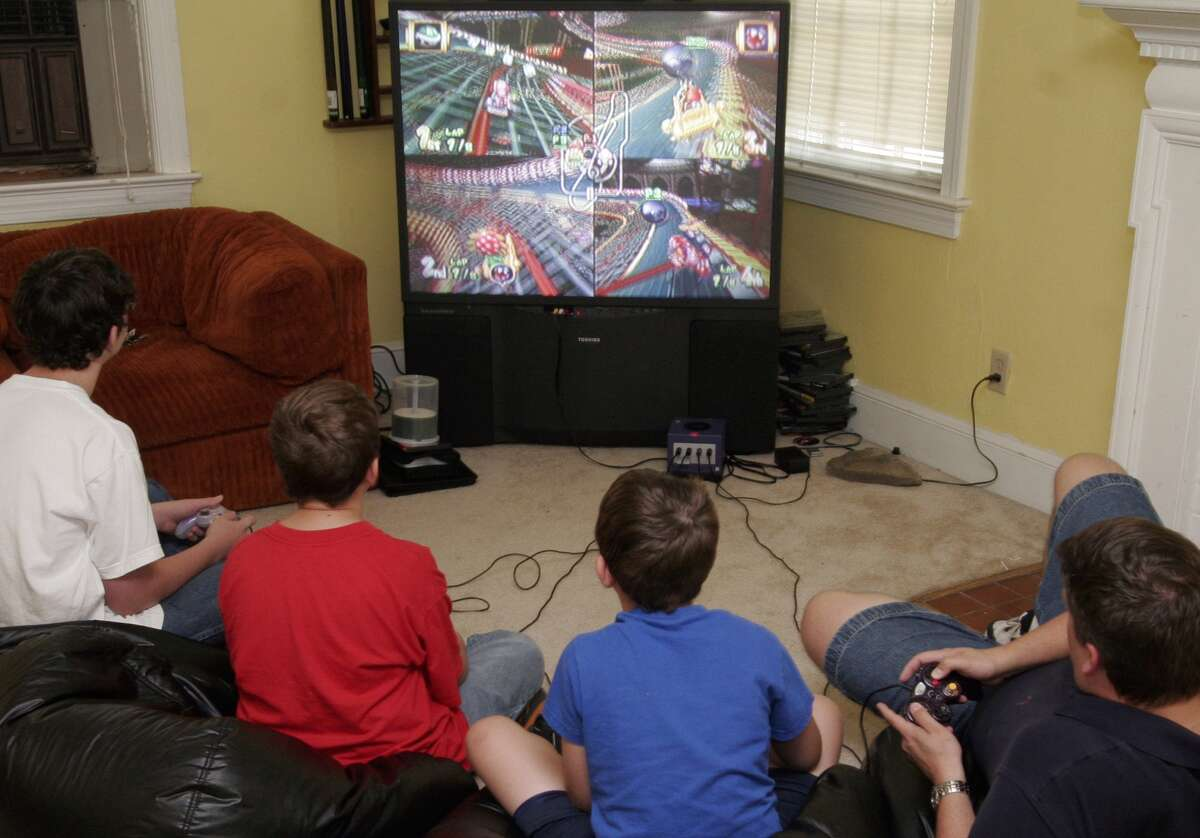 PICTURED, from left to right, Chris Palamore, 12, Curtis Palamore, 10, Matthew Palamore,8, and their father Brad Palamore enjoying a game of Mario Kart Double Dash.