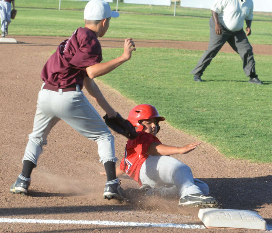 Plainview Red's Mark Garcia tries to slide under the tag of Hereford third baseman Jordyn Valdez in the second inning of an 11-12-year-old 70-foot district game at McMillan Field Friday night. Garcia was called out on the play. Hereford edged Plainview 7-5 in the opening-round game. Plainview Red will play at 11 a.m. Sunday. Photo: Skip Leon/Plainview Herald