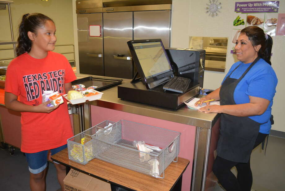 YMCA safe camper Zayla Moreno, 10, gets ready to eat thanks to Rose Mary Flores and the staff of Aramark and the Plainview ISD cafeteria staff. Summer breakfast and lunch meals are offered free of charge to all kids. Photo: HOMER MARQUEZ/PLAINVIEW HERALD