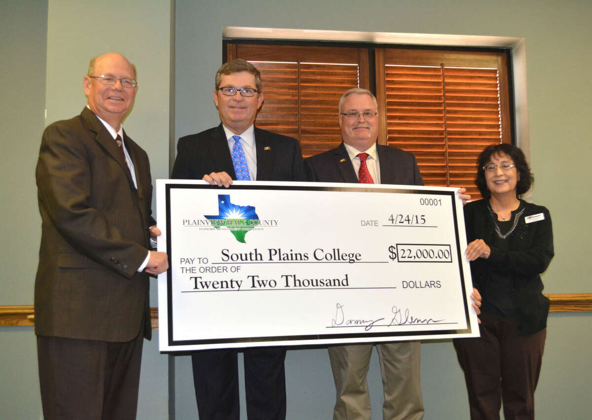 """Doug McDonough/Plainview HeraldPlainview/Hale County Economic Development Executive Director Mike Fox (left) presents South Plains College President Dr. Kelvin Sharp, Workforce Development Coordinator-Plainview Paul Henderson, and Plainview Campus director Gracie Quinonez with a mock check representing a $22,000 Economic Development Incentive Grant. The funds are to purchase 12 Allen Bradley programmable logic controllers to train students at the local campus. Henderson explains, """"The units have thousands of industrial applications, including wind energy and are used by most large corporations."""""""