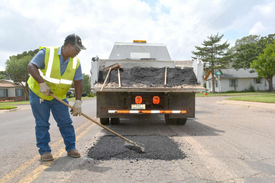 "Veteran city employee Jimmy Collins smooths an asphalt mixture over a rough portion of pavement on West 11th Street on Tuesday as part of the city's routine summer street maintenance program. Called a ""street overlay,"" the spot treatments will keep freezing moisture from penetrating the pavement during winter. Otherwise, repeated freezing and thawing will case the pavement to break apart."