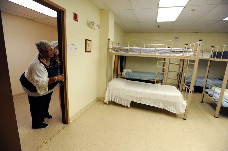 Velma Clark pops her head into one of the several shared bedrooms inside the Pacific House homeless shelter. Photo: Michael Cummo / Hearst Connecticut Media / Stamford Advocate