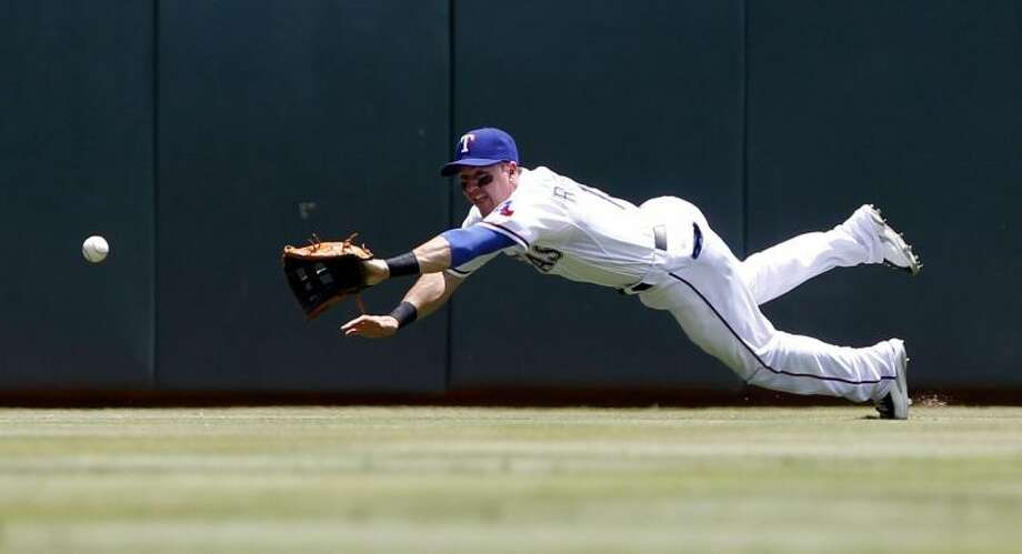 Texas Rangers center fielder Dan Robertson dives for a ball in a game against the Los Angeles Angels Sunday. Robertson is one of the young players the Rangers have employed in the first half of the season as they've been ravaged by injuries. Photo: Richard W. Rodriguez/Fort Worth Star-Telegram/MCT