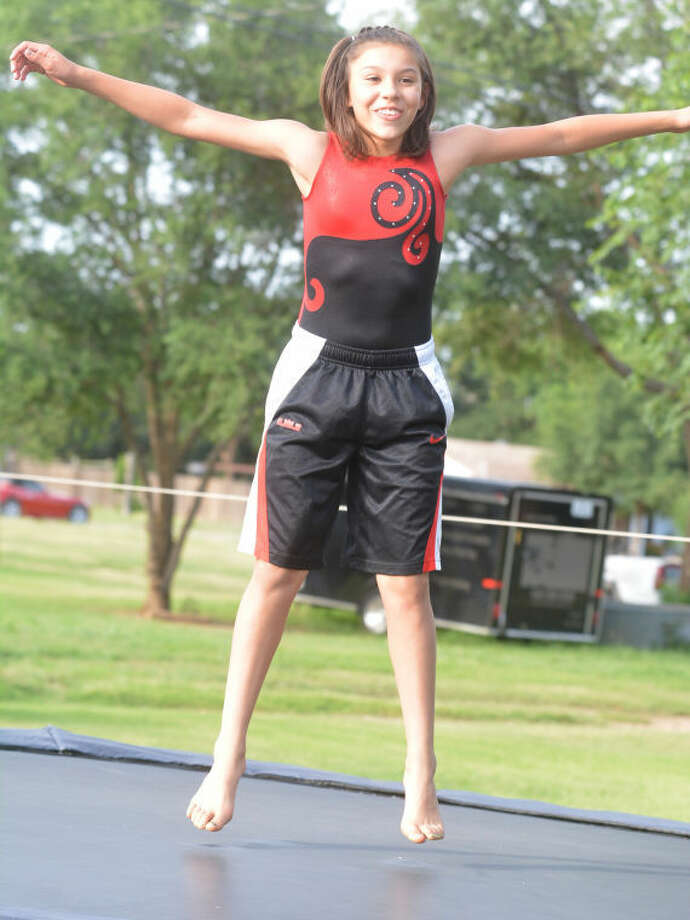 Makenzy Corrales jumps on the trampoline in her backyard in Earth, Tex. She has been taking lessons for two years at Gifted and Talented Gymnastics in Plainview under the tutelage of Jesse Camargo. Photo: Skip Leon/Plainview Herald
