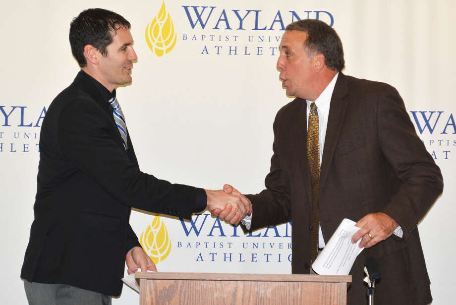 Ty Harrelson, left, shakes hands with Director of Athletics Rick Cooper as he is introduced as the new Wayland Baptist University men's basketball coach at the Hutcherson Center Monday afternoon. Harrelson, who played for the Pioneers from 2001-03, takes over for Matt Garnett, who resigned last month to leave coaching and take a teaching job in Fort Worth. Photo: Skip Leon/Plainview  Herald
