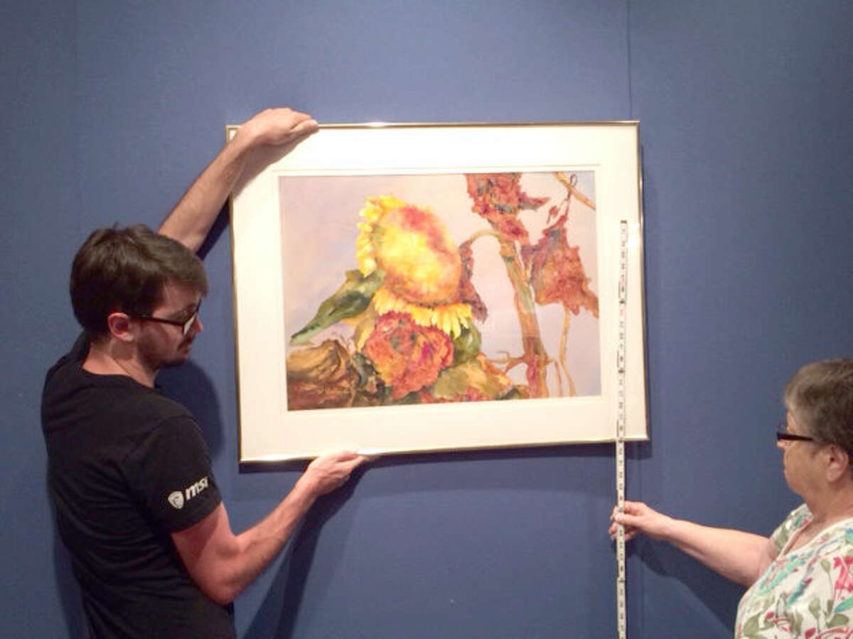 """Courtesy Photo In preparation to """"COLLECTED,"""" the current exhibit Abraham Art Gallery on the Wayland Baptist University campus, gallery assistants Jon Riddle and Jeanette Curry hang one of the painting for the show. The exhibit continues until Aug. 21."""