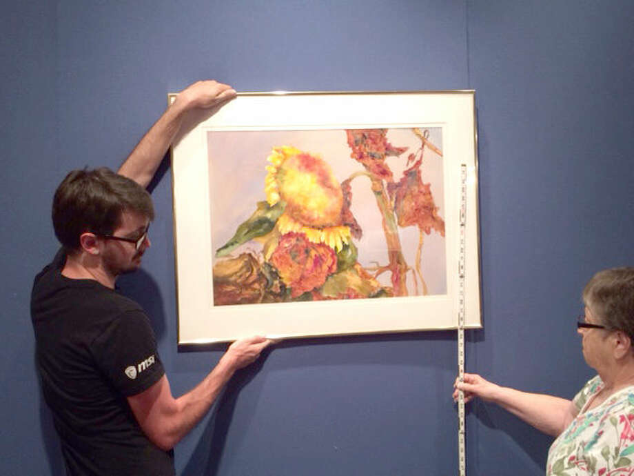 "Courtesy Photo In preparation to ""COLLECTED,"" the current exhibit Abraham Art Gallery on the Wayland Baptist University campus, gallery assistants Jon Riddle and Jeanette Curry hang one of the painting for the show. The exhibit continues until Aug. 21."