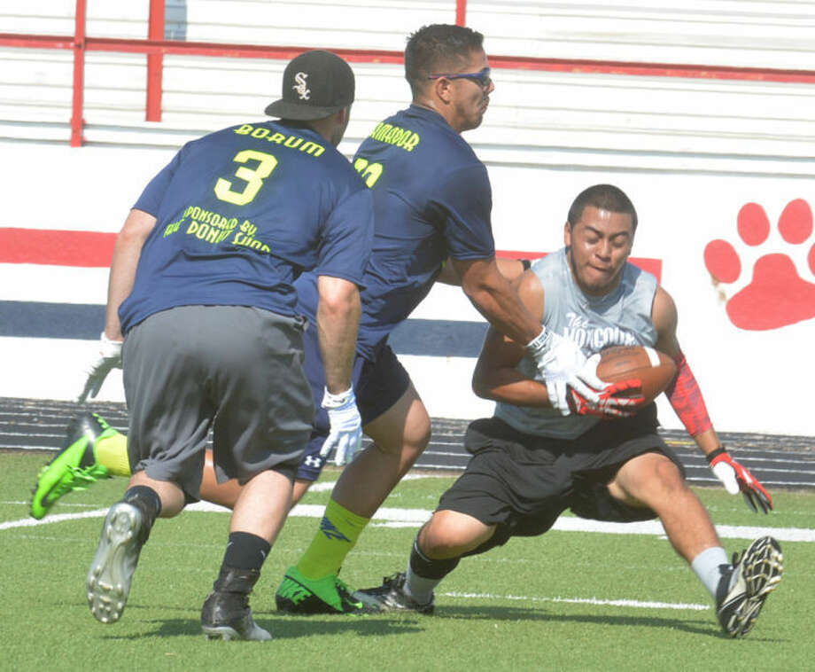 Receiver Paul Lara tries to make a move against two defenders during the Snack Pak 4 Kids Plainview Flag Football Tournament last week. Photo: Skip Leon/Plainview Herald