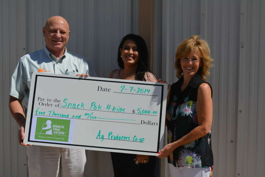 Dave Rienders, general manager of Ag Producers Co-op, presents Snack Pak 4 Kids representatives Carmen Ortega and Susan Hurt (left) with a donation to fund the weekend hunger program.
