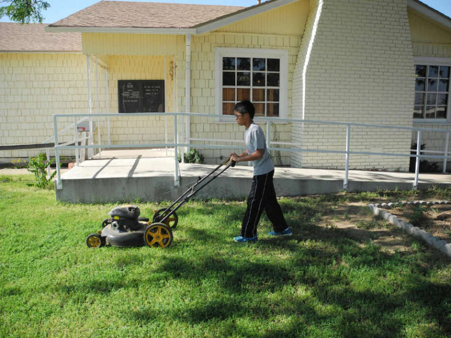 Kevin Bahn of FUMC cuts the grass in front of Compassionate Care Pregnancy Center on Saturday as part of the church's Day of Service. Photo: Gail M. Williams | Plainview Herald