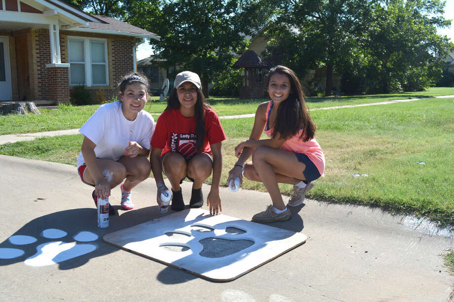 Making TracksDoug McDonough/Plainview HeraldAs an annual fundraiser, Plainview High School cheerleaders are painting PHS Bulldog paw prints on driveways and sidewalks. One of the paint crews last weekend included Dareli Chavez (left), jayvee; Bailey Cantu, varsity; and Kassandra Torres, freshman. Cost is $10 for the first paw print and $5 for each additional print. The fundraising drive continues throughout the end of the week. Contact Cindi Weiland, PHS Cheer Booster Club president, at 806-292-7541 to or order a paw print.