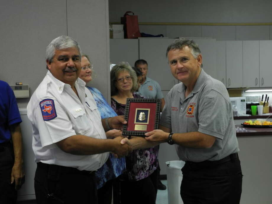 Fire Chief Rusty Powers presents Capt. Albert Perez with a plaque for his 39 years of service. Perez celebrated his last day at the fire station Monday. Photo: Gail M. Williams | Plainview Herald
