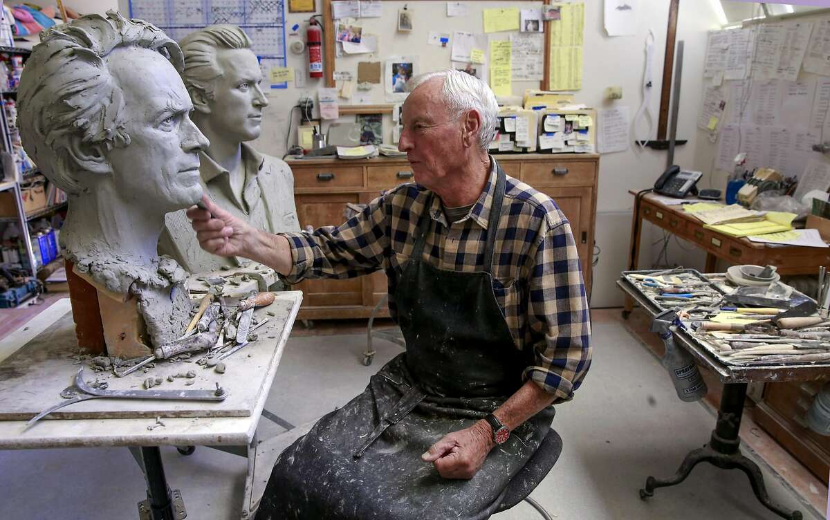Bruce Wolfe works on his creations of Clint Eastwood, (left) and Gavin Newsom, at his home studio in Oakland, California, on July 19, 2016. Wolfe is in the final stages of completing a full size bronze of singer Tony Bennett that will be placed outside the Fairmont Hotel.