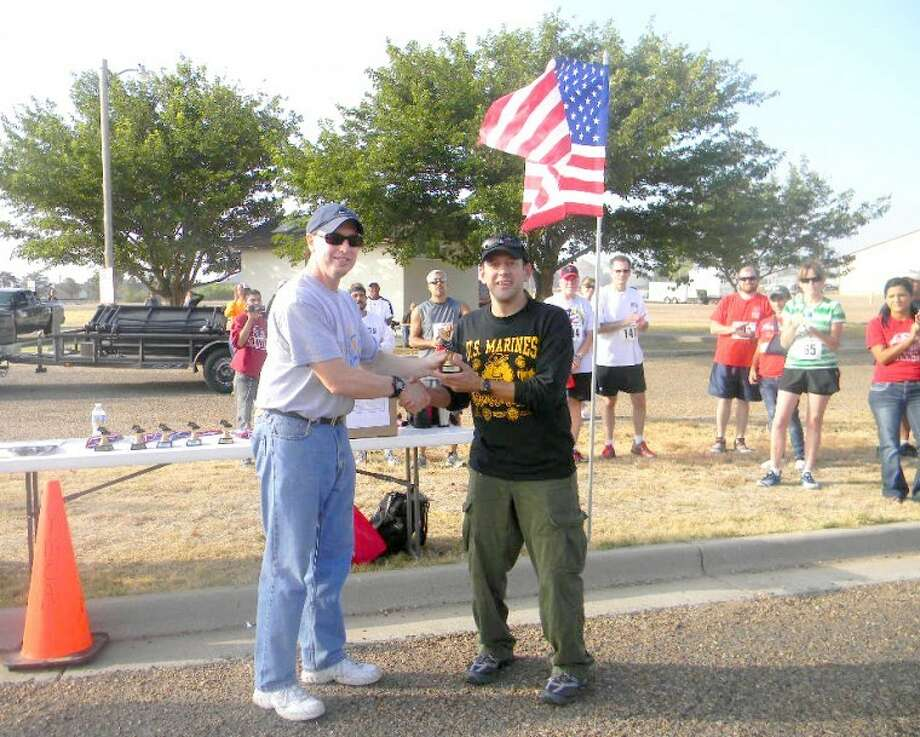Event organizer Ron Appling (left) presents Martin Montalov with the trophy for being top racer overall in Saturday's Hale on Feet 5K Run. The 46-year-old completed the Cowboy Days event in 19.11 minutes.