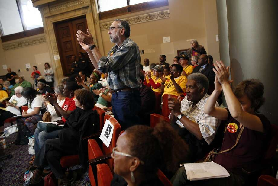 Michael Kauffman applauds a speaker during the discussion of stricter rent control measures at Tuesday's Oakland City Council meeting. Photo: Scott Strazzante, The Chronicle