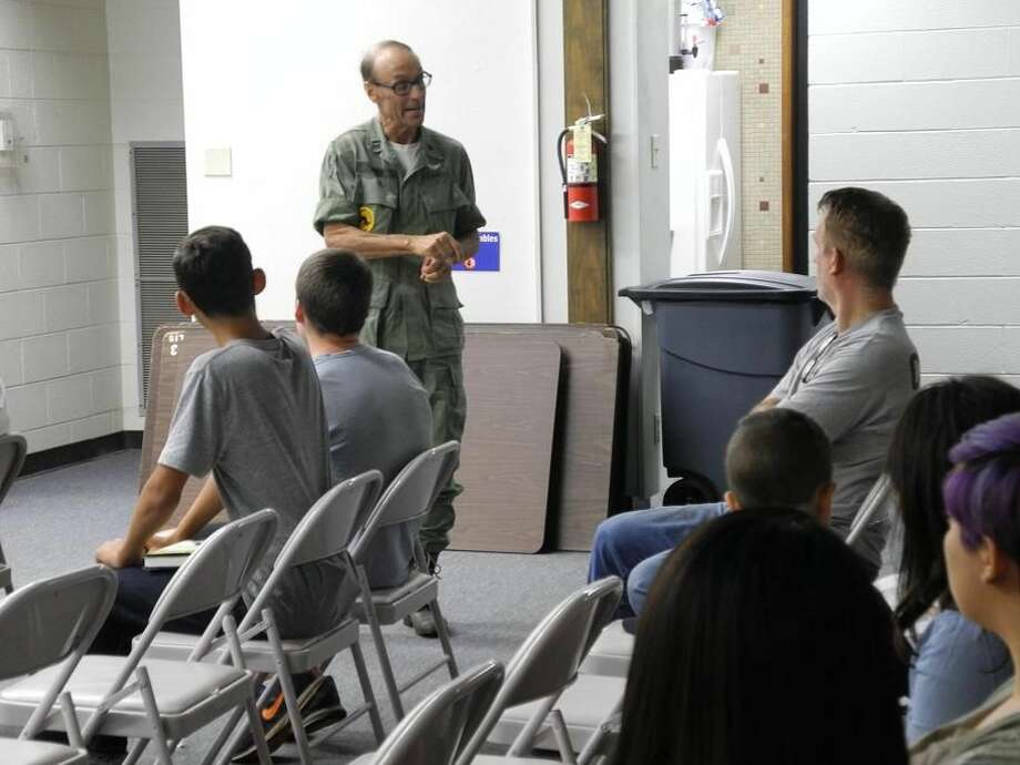 "Bob Ford, author of ""Black Cat 2-1: The True Story of a Vietnam Helicopter Pilot and His Crew,"" visits with young people in the audience before beginning his lecture. Photo: GAIL M. WILLIAMS/Herald Correspondent"