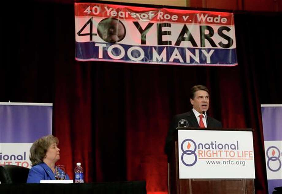 Carol Tobias, president of National Right To Life, left, watches as Gov. Rick Perry delivers a speech to a large audience in attendance at the national convention, Thursday, June 27, 2013, in Grapevine, Texas. The Republican has called a second special legislative session beginning July 1, allowing the GOP-controlled statehouse another crack at passing restrictions opponents say could shutter nearly all the abortion clinics across the country's second-largest state. (AP Photo/Tony Gutierrez) Photo: Tony Gutierrez / AP