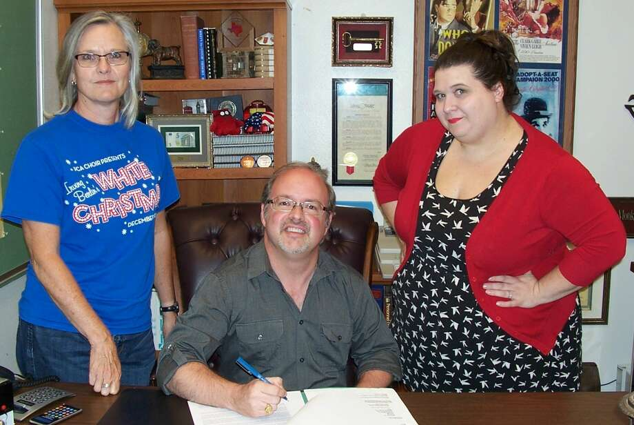 Plainview Repertory Theatre members Marla Maresca (left) and Heather May look on as Fair Theatre Manager Shane Harrell signs an agreement which grants the civic theatre group a home base. The partnership will result in more quality shows being brought to the local stage and will provide space for various acting academies throughout the year.