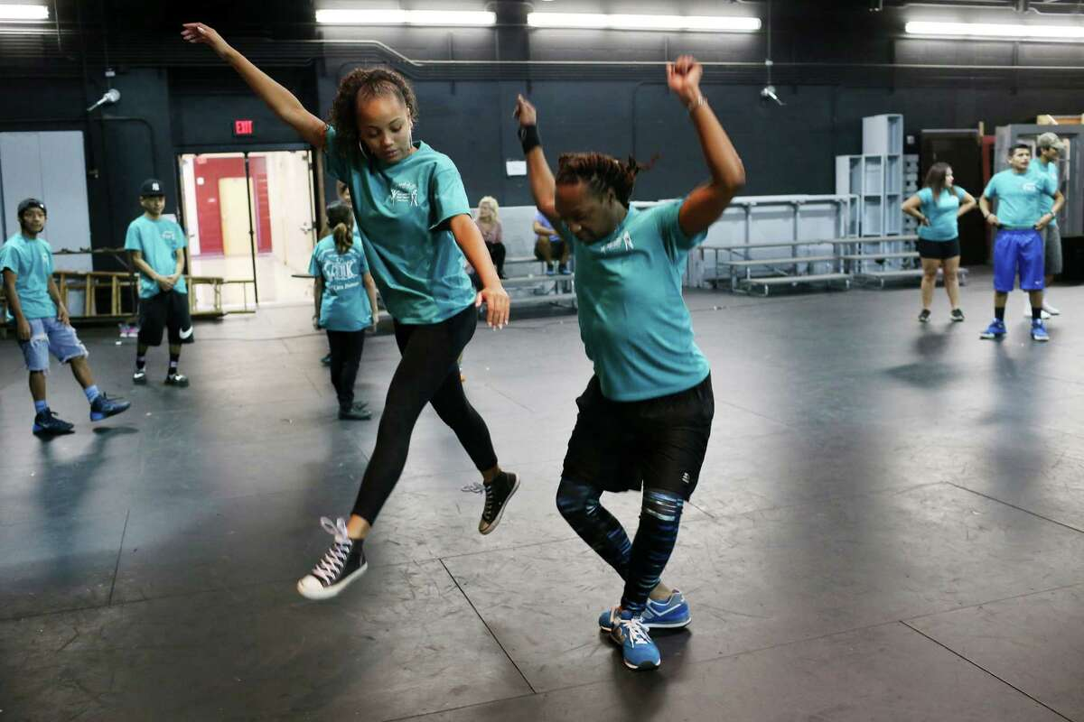 Instructor Mervin Primeaux-OBryant, right, helps Justina Miles, 13, with a move as students with the San Antonio Deaf Dance Company rehearse at the Marshall High School auditorium, Tuesday, July 19, 2016. The students will have their recital on July 29. The San Antonio Deaf Dance Company is celebrating its 20th anniversary. It's a leadership program for local middle and high school students who are deaf or hard of hearing. They have a month-long dance camp every summer. This year 32 students are in the program.