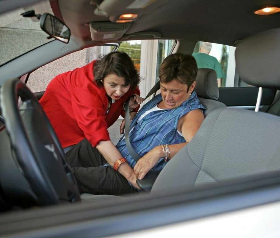 American Cancer Society/Courtesy PhotoThe American Cancer Society is in dire need of Road Drivers in Plainview/Hale County. Here a volunteer helps a cancer patient buckle up for the ride.
