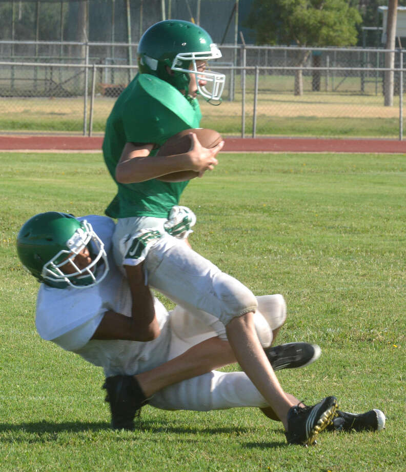 A Floydada receiver is dragged to the ground by a defensive back during the Whirlwinds' practice Thursday morning. Floydada will see its first game action today when they travel to Wellington for a scrimmage against the defending Class A Division II state champion Rockets at 5 p.m. Photo: Skip Leon/Plainview Herald
