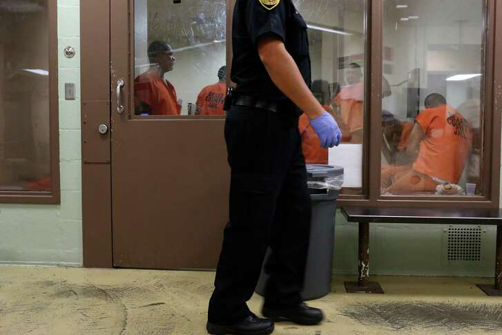 Inmates wait in a holding unit in the intake area of the Bexar County Jail, Monday, July 18, 2016. The inmate's evaluated for mental and physical health problems before being released into the jail population. Between the beginning of the year and July 14 there have been 924 suicide attempts at the jail. Three inmates have died as a result, all in the last three weeks.