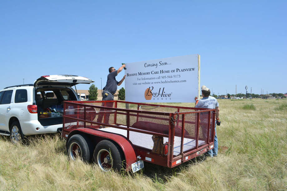 Doug McDonough/Plainview Herald Chris Arellano (left) and Fidencia Cantu of Sir Speedy signs in Amarillo erect a sign in the 1500 block of Mesa on Tuesday indicating that BeeHive Memory Care Home will be built on that location. The Plainview City Council must first approve a plat for the location before construction can begin, likely not until after the first of the year. The BeeHive sign permit is one of 17 building permits issued in August by the city.