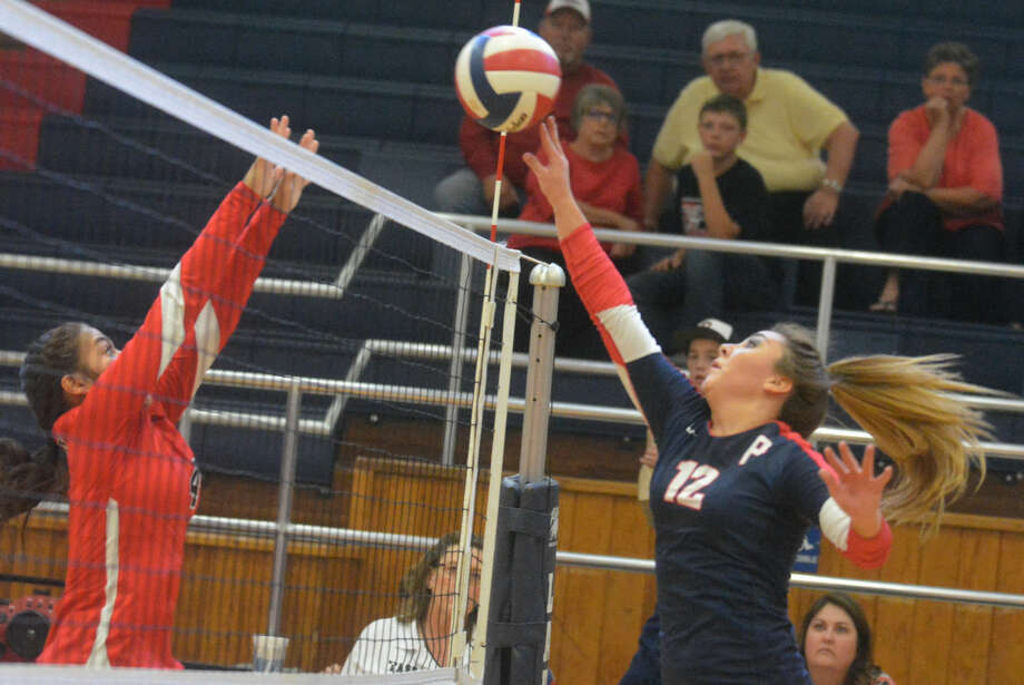 Plainview's Shadee Tye (right) tips the ball over the net as a Brownfield player tries to make the block during a volleyball match at the PHS gym Tuesday. The Lady Bulldogs swept to a three-game victory. Photo: Skip Leon/Plainview Herald