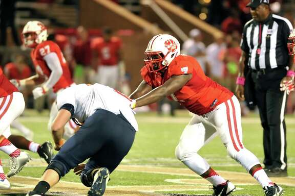Katy High School defeated Seven Lakes, 41-8, in a game played at Rhodes Stadium, 10-10-15. Right, Katy defensive lineman Corey Bethley (7) fights off a block by Seven Lakes' Trace Oldner (73).