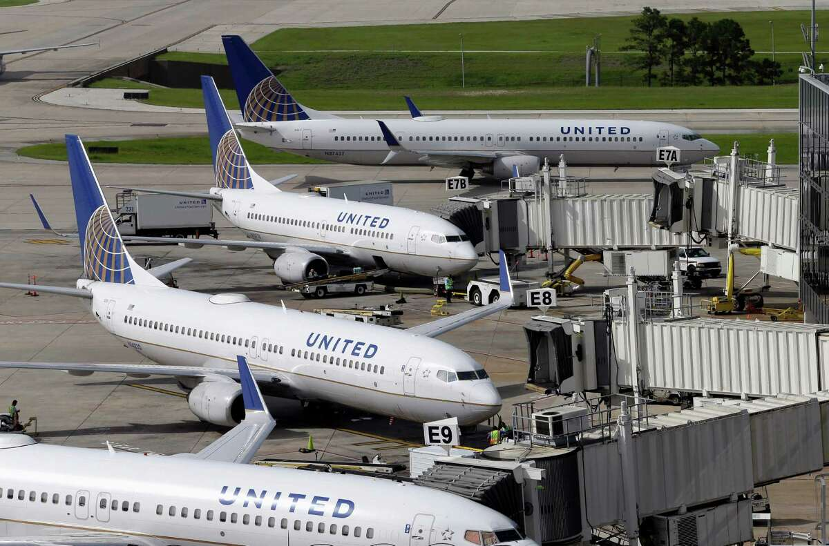 FILE - In this July 8, 2015, file photo, United Airlines planes are parked at their gates as another plane, top, taxis past them at George Bush Intercontinental Airport in Houston. (AP Photo/David J. Phillip, File)