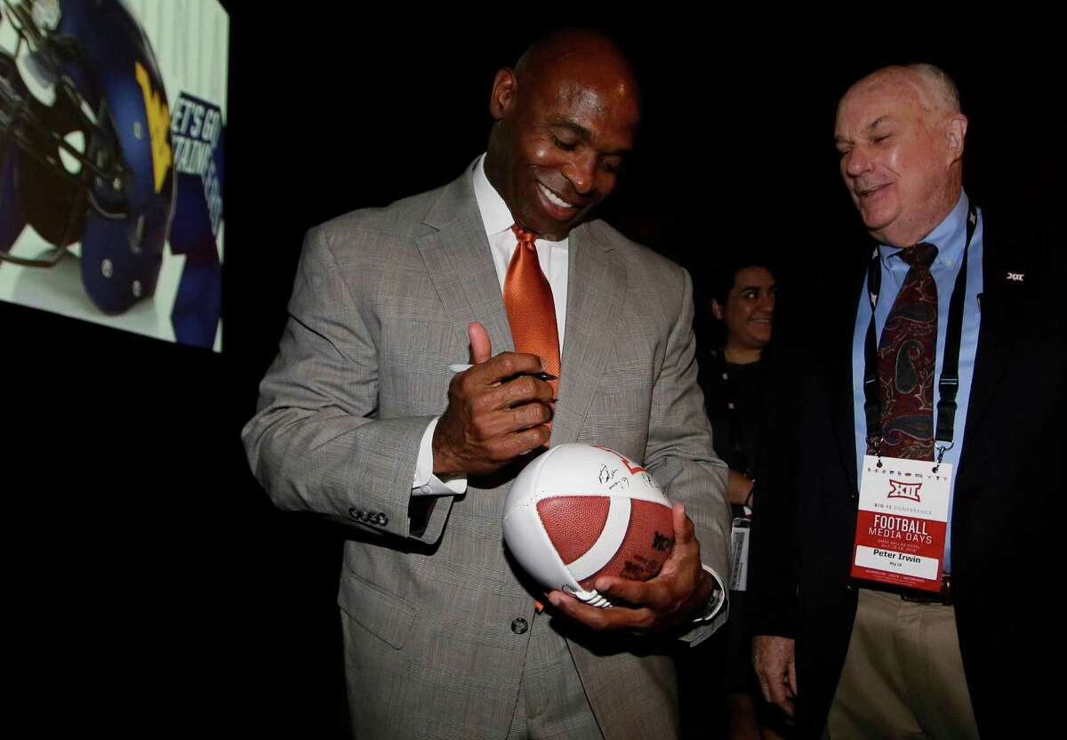 Texas coach Charlie Strong, left, is happy to oblige an autograph seeker Tuesday.