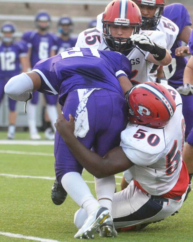Plainview defenders Roy Abanonu (50) and Brian Switzenberg (15) team up to tackle Canyon's Nathan Spencer (21) during last week's game. Photo: Skip Leon/Plainview Herald